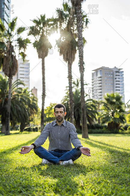 Man sitting on meadow in city park doing yoga exercise