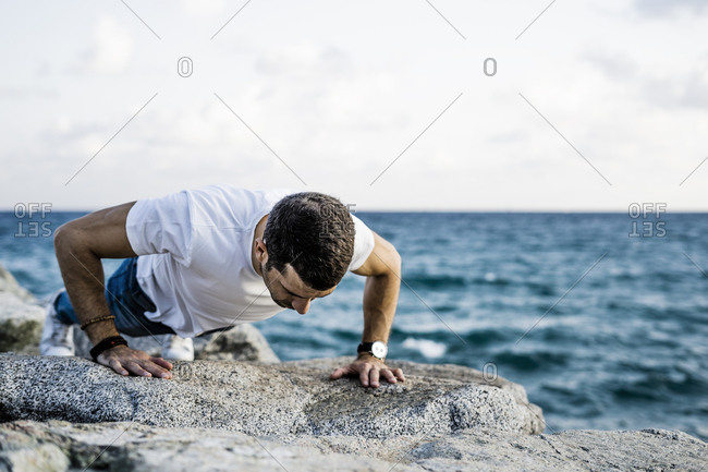Man doing doing pushups on rock in front of the sea
