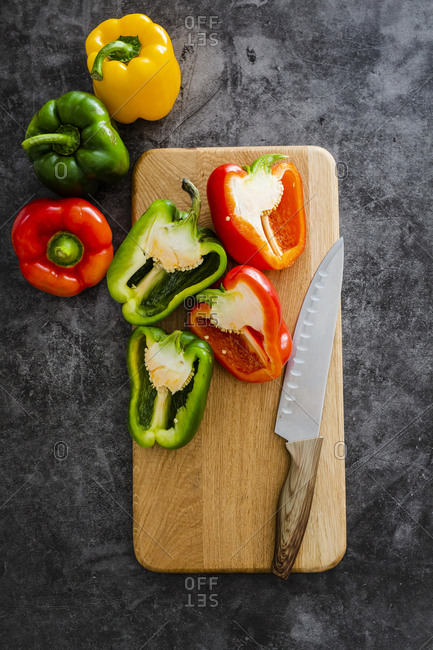 Green and red bell peppers on chopping board- chopping