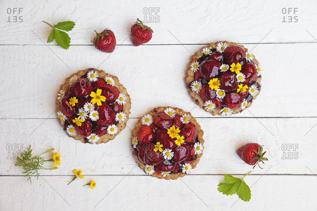 Homemade strawberry heart tartlets with daisy flowers and golden marigold- edible flowers- white wood