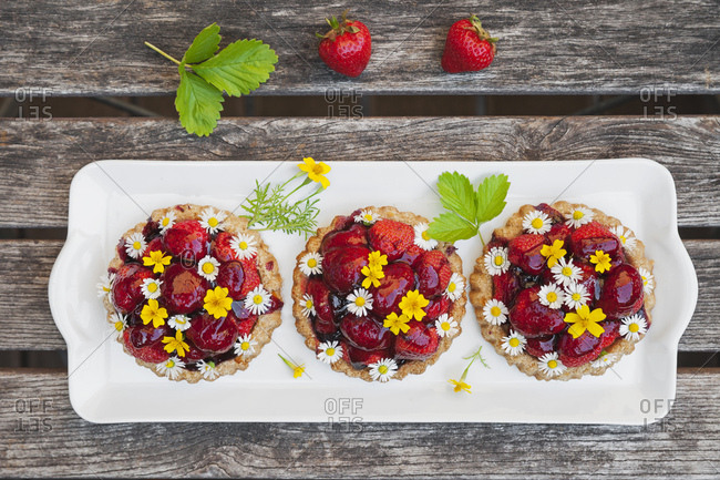 Homemade strawberry heart tartlets with daisy flowers and golden marigold- edible flowers- dark wood
