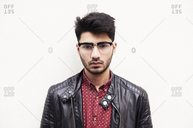Portrait of handsome bearded guy in stylish glasses and leather jacket over white background