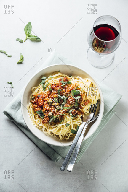 Spaghetti with tomato caper sauce- basil and parmesan with a glass of red wine