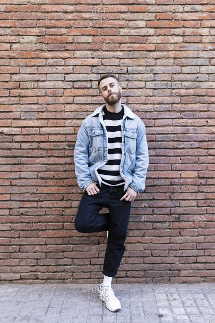 Portrait of a cool man standing at a brick wall