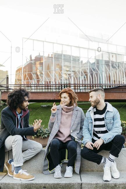 Three friends sitting in the city talking