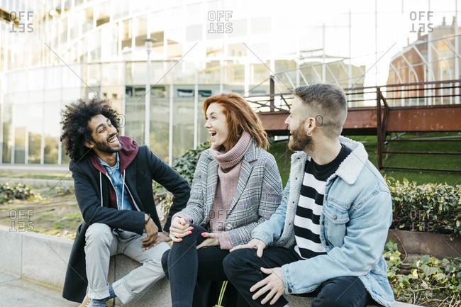 Three happy friends sitting in the city talking