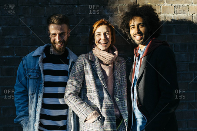 Portrait of three happy friends in shadow at a brick wall
