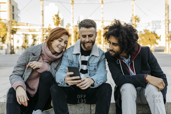 Three happy friends sitting outdoors looking at cell phone