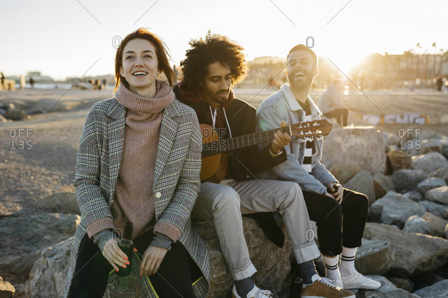 Three happy friends with guitar sitting outdoors at sunset