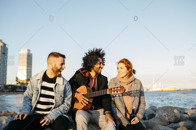 Three happy friends with guitar sitting outdoors at the coast sunset