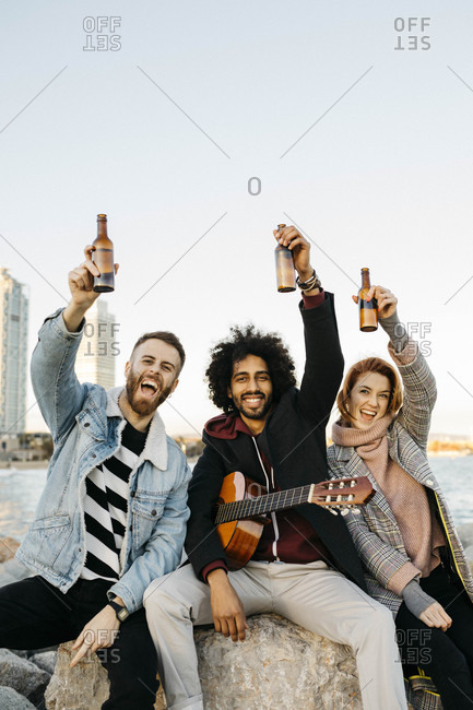 Portrait of three happy friends with guitar raising beer bottles at the coast sunset