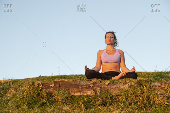 Woman meditating on a meadow in the evening