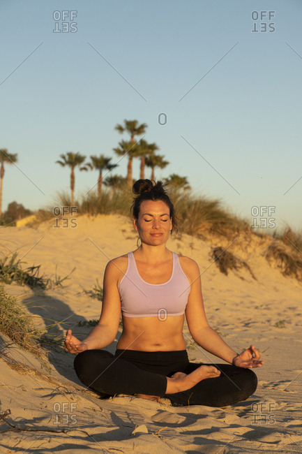 Woman meditating on the beach in the evening