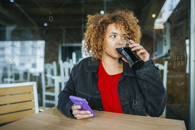Young woman with cell phone drinking cola at a bar