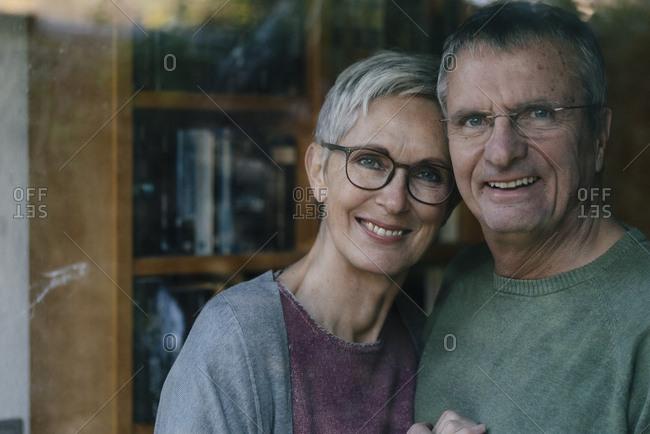 Portrait of happy senior couple behind windowpane
