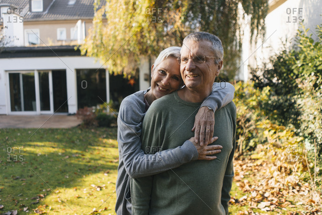 Happy affectionate senior couple hugging in garden