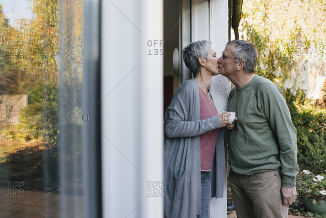 Affectionate senior couple kissing at terrace door