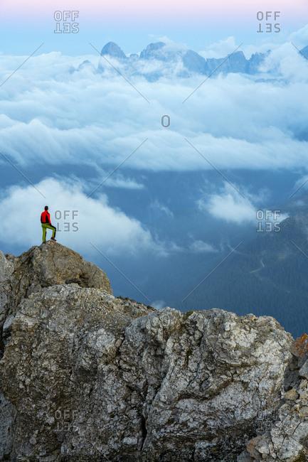 Italy- Veneto- Dolomites- Alta Via Bepi Zac- mountaineer standing on Pale di San Martino mountain at sunset