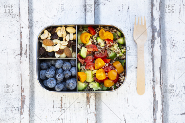 Lunch Box with quinoa salad with tomato and cucumber- blue berry and trail mix