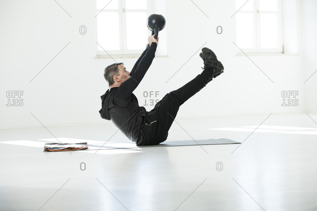 Man doing his fitness regime- doing kettle bell sit-ups
