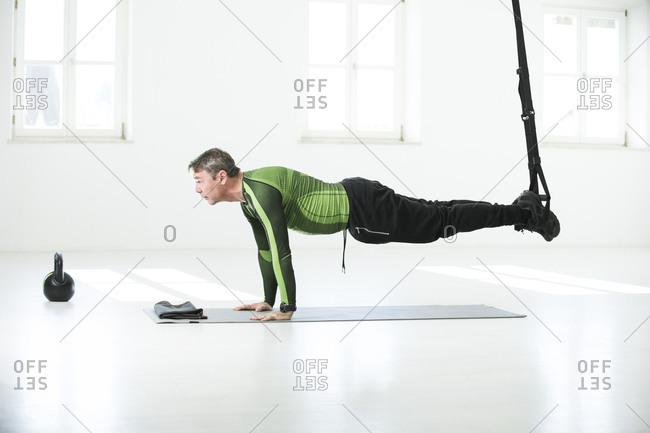 Man doing his fitness regime- doing suspension training