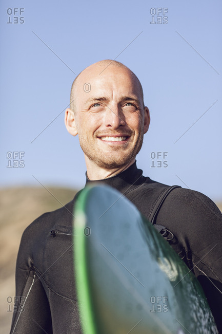 Portrait of smiling surfer with surfboard