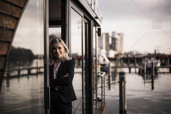 Businesswoman standing on a houseboat- looking out of window
