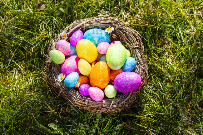 Multicolored Easter eggs in a nest on grass