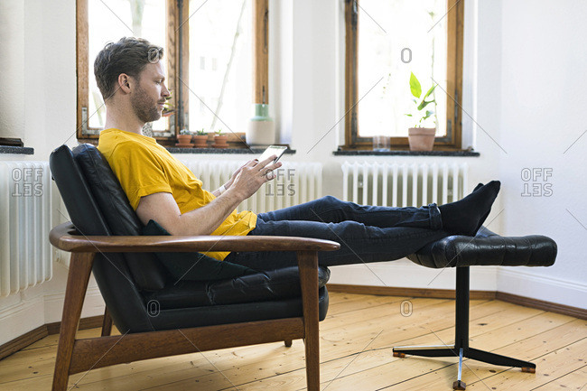 Casual man  in yellow shirt sitting in Lounge Chair in stylish apartment looking on tablet