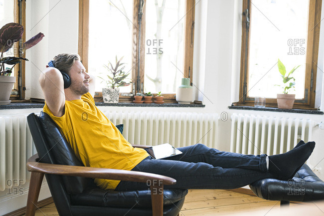 Rrelaxed man in yellow shirt with headphones sitting in Lounge Chair in stylish apartment
