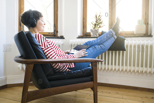 Short-haired woman with headphones relaxing in lounge chair in stylish apartment