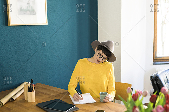 Businesswoman in home office writing on a piece of paper holding coffee mug