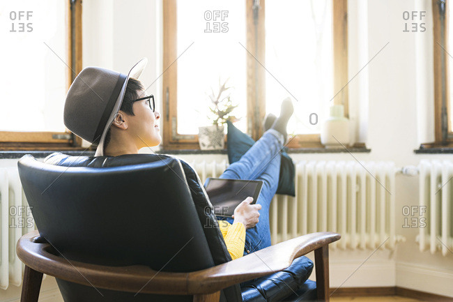 Woman relaxing in lounge chair holding a tablet and looking outside windows in stylish apartment
