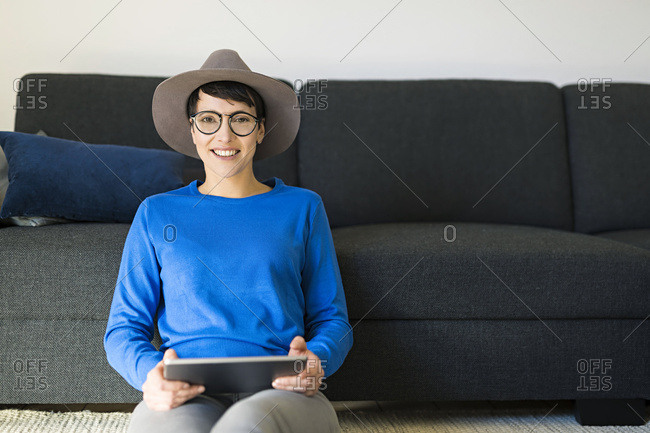 Portrait of smiling woman in living room using a tablet