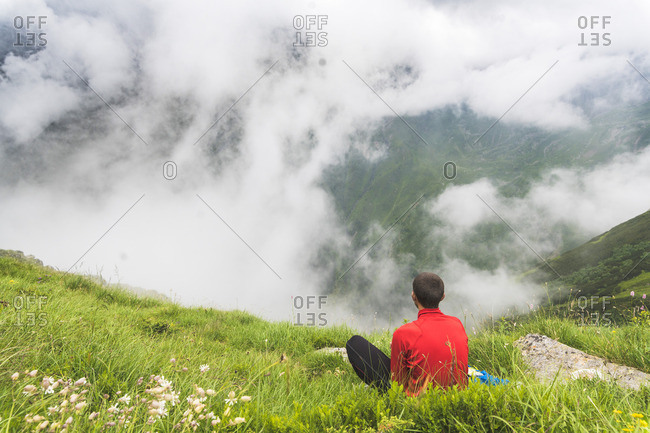Man taking a break from his hike-sitting in the grass in the Carpathian Mountains- Romania