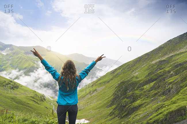 Happy woman raising her arms and looking over the Carpathian Mountains- Romania