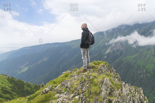 Man standing on top of a hill and looking at the landscape in the Carpathian Mountains- Romania