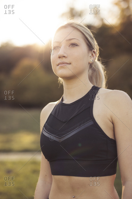 Portrait of young sportive woman against evening sun