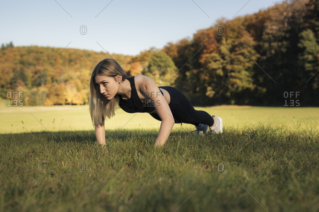 Young woman doing pushups during workout on meadow