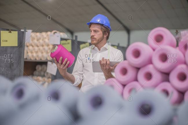 Man wearing hard hat checking delivery in factory