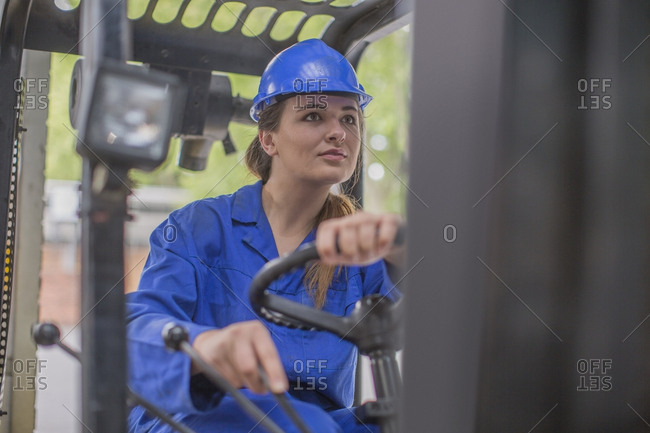 Woman wearing hard hat driving forklift in factory