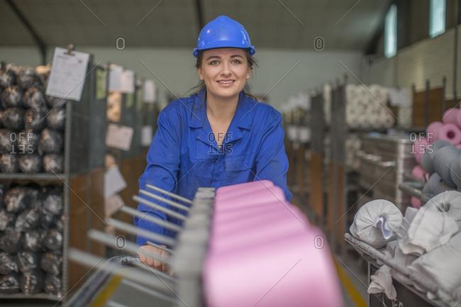Portrait of smiling woman wearing hard hat in factory