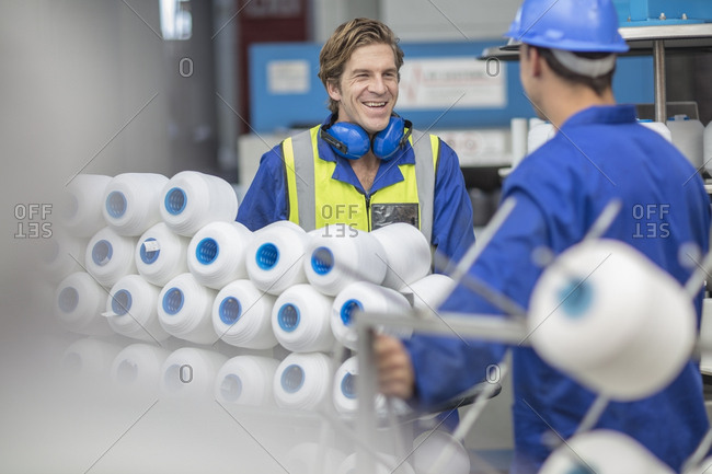 Worker wearing reflective vest smiling at colleague in factory