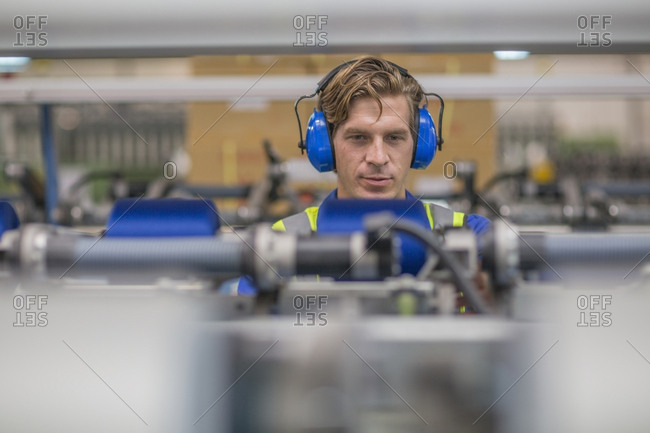 Man wearing ear defenders operating machine in factory