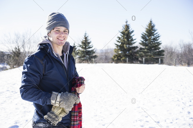 Young man portrait playing in the snow during Canadian winter