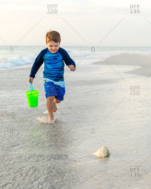 Young Excited Child Runs Toward a Seashell on the Beach