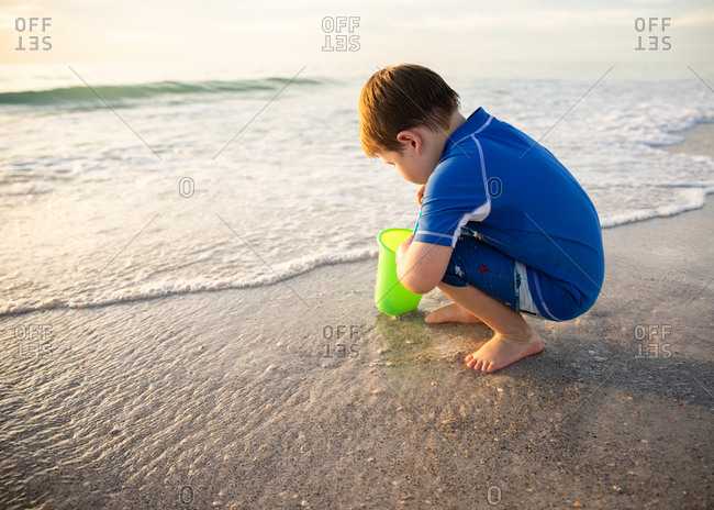 Child Kneeling with Bucket Searching for Seashells on the Shore