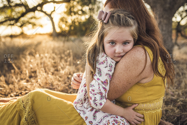 Close up of young girl embraced by mother in California field