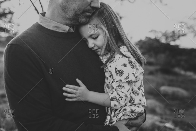 Close up of daughter being embraced by father in California field
