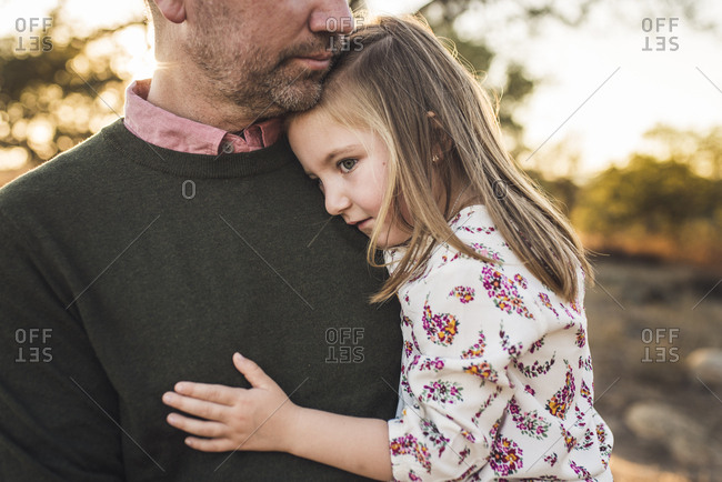 Close up of young girl being embraced by father in California field
